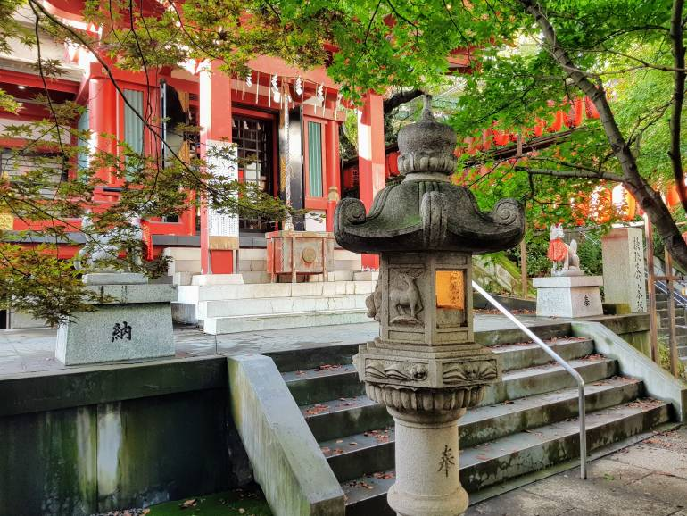 A stone lantern in the foreground with steps and a Shinto prayer hall in the background