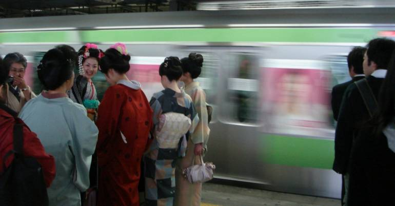 Kimono-clad women waiting for a train.