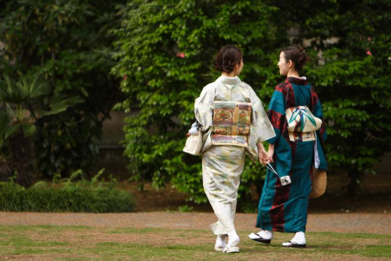Two women in kimono go for a stroll and discuss ways to save money.