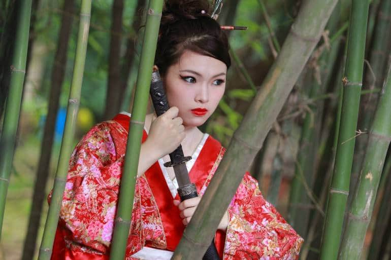 Once you've got your cheapo kimono, all you need is a sword and bit of bamboo to complete your Japan experience. Woman in bamboo forestpic via Shutterstock.