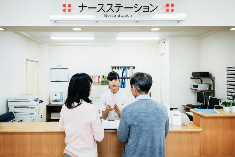 A nurse is talking to a couple and going through details of their stay at a Japanese Hospital.
