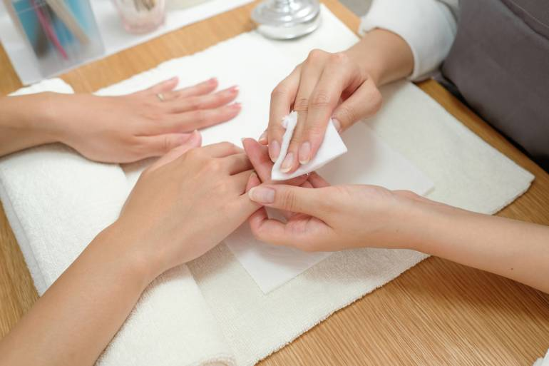 Nail stylist doing nail care treatment