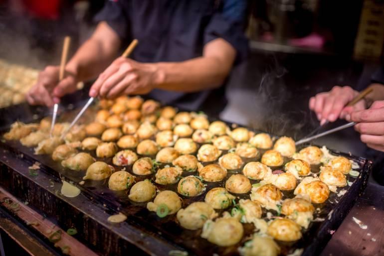 Chef turning takoyaki on a grill