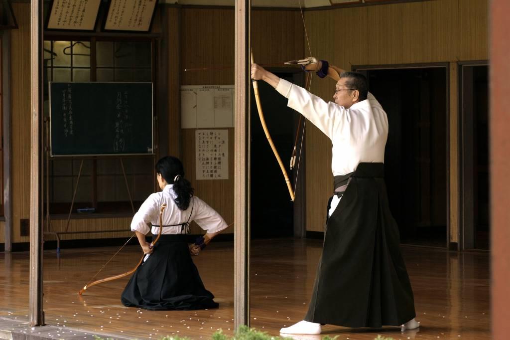 Kyudo Japanese archery. Man takes aim while woman prepares her next shot.