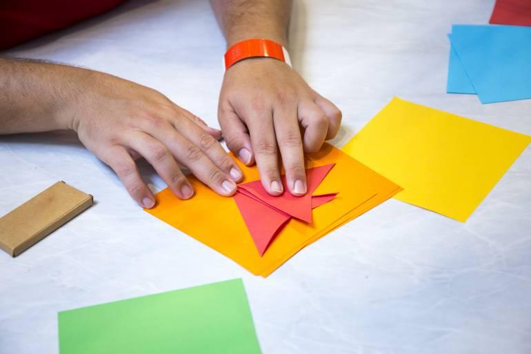 A man folding color paper