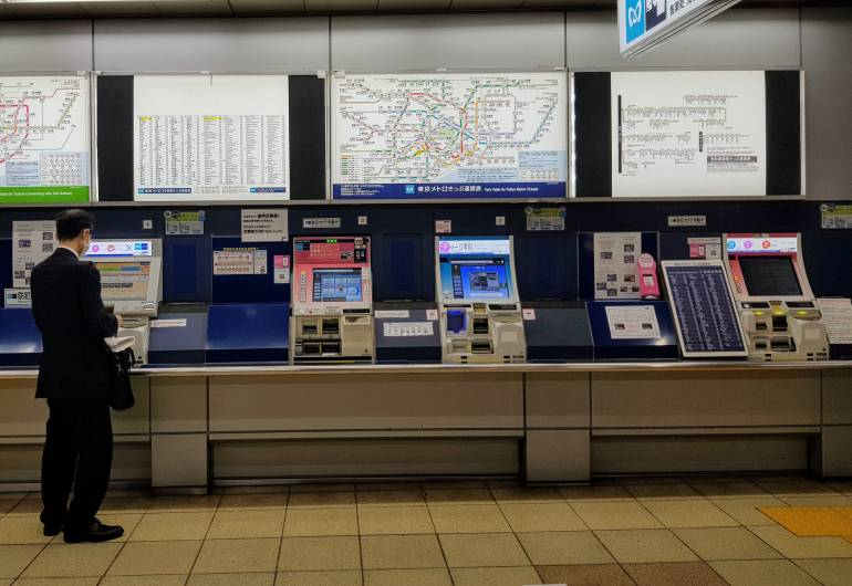 An array of ticket machines below a network map at Tokyo Metro Akasaka Station