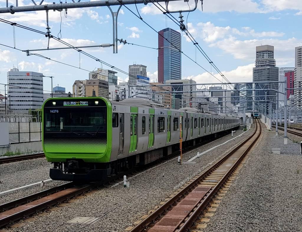 A Yamanote Line E235 series EMU approaching Takanawa Gateway Station