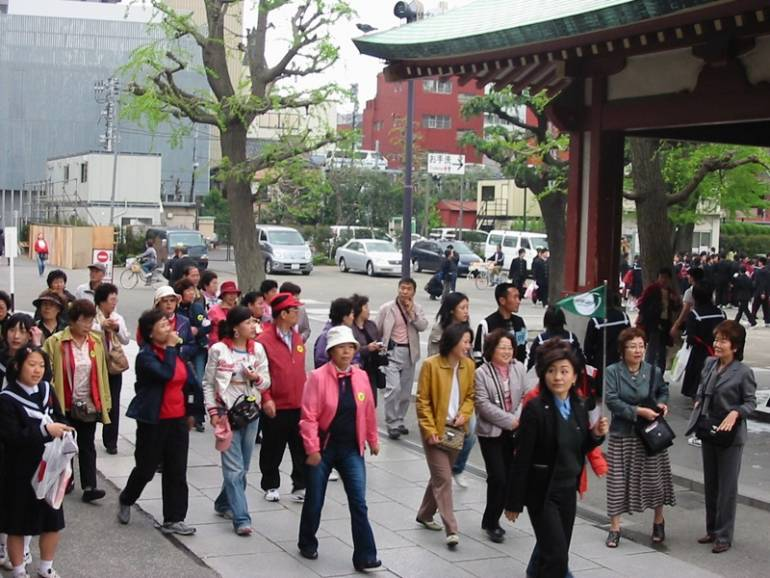 A tour guide in Tokyo leads a group.