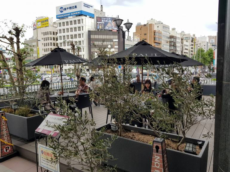 Paul Yotsuya terrace. People seated at tables with umbrellas and small olive trees.