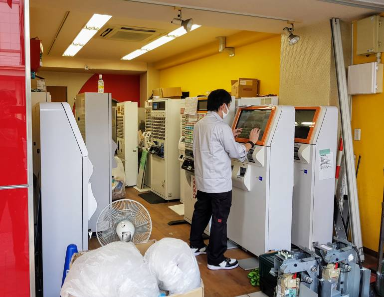 Man programming restaurant ticket vending machines