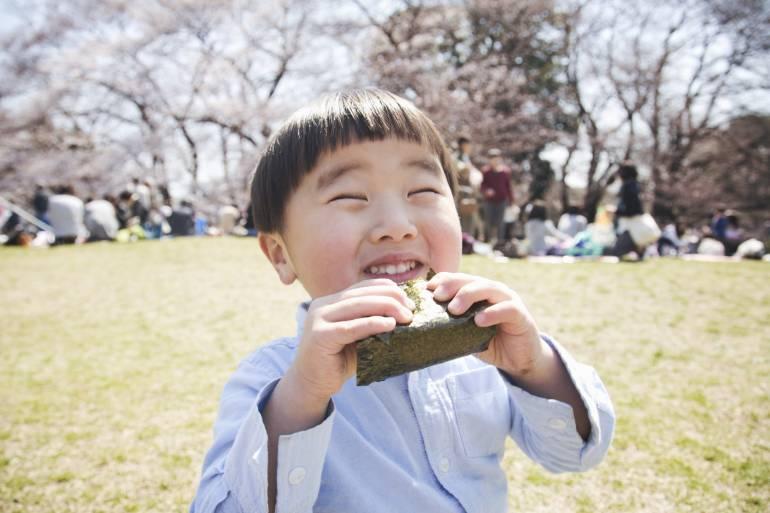 Boy eating a Japanese rice ball.