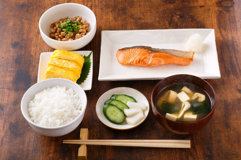 A traditional Japanese breakfast with salmon, tamagoyaki, natto, miso soup and rice.