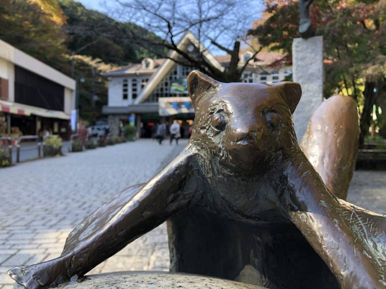 flying squirrel statue with cable car station at takao-san