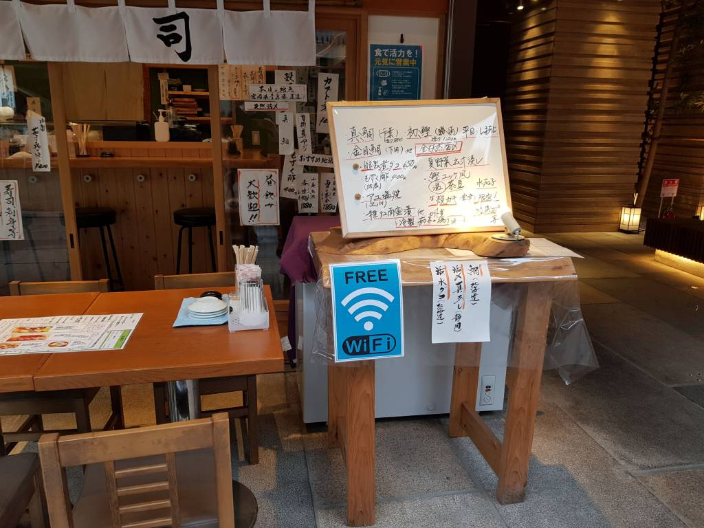 A sushi shop with a free wi-fi sign outside