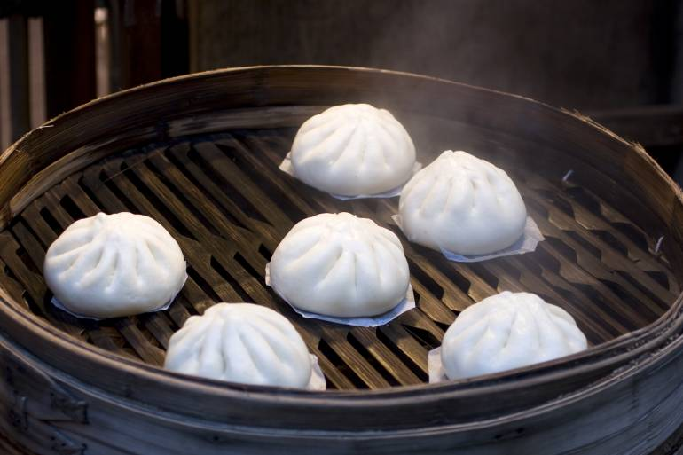Nikuman buns with meat, steaming on a grill