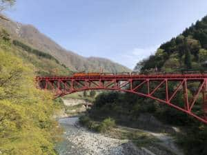 Kurobe Gorge Railway train crossing bridge
