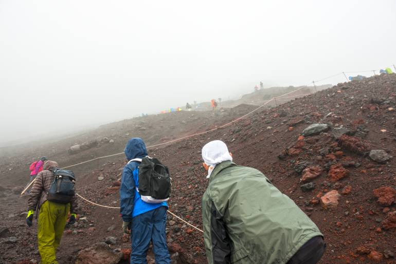 Hikers in raincoats climb across loose scoria on Mt. Fuji. It's foggy and they're holding on to guide ropes.