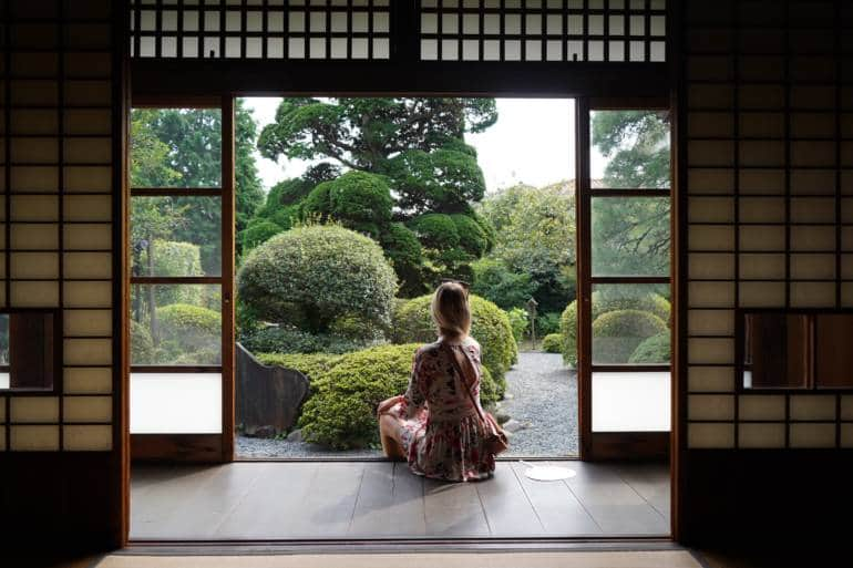 a woman looks into a Japanese garden