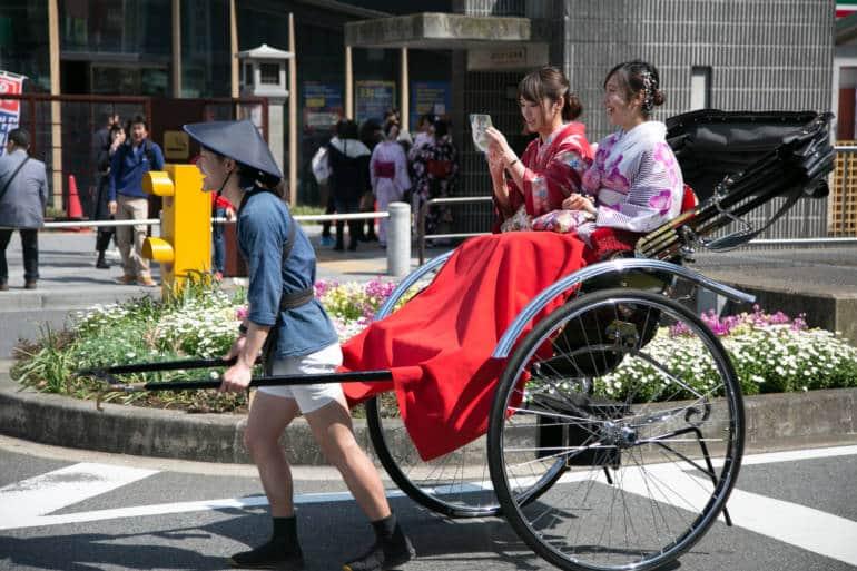Rickshaw driver pulling two women in kimono