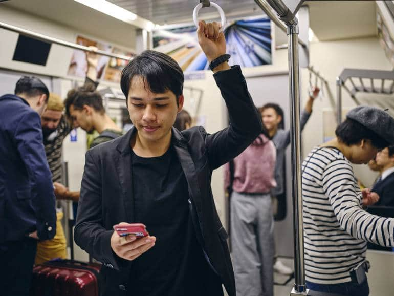 man with phone on japanese train