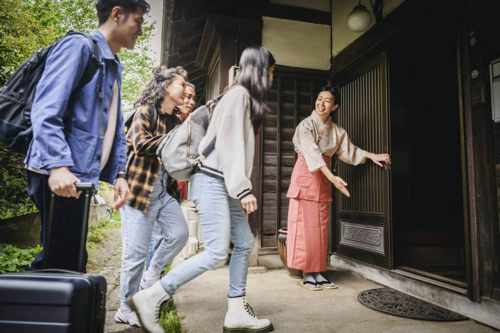 Japanese women welcoming four backpackers with luggage, opening door, ushering them inside the building