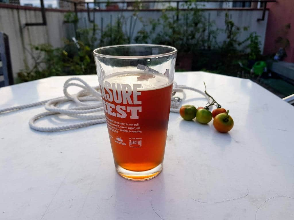 A glass of beer, outside with some tomatoes