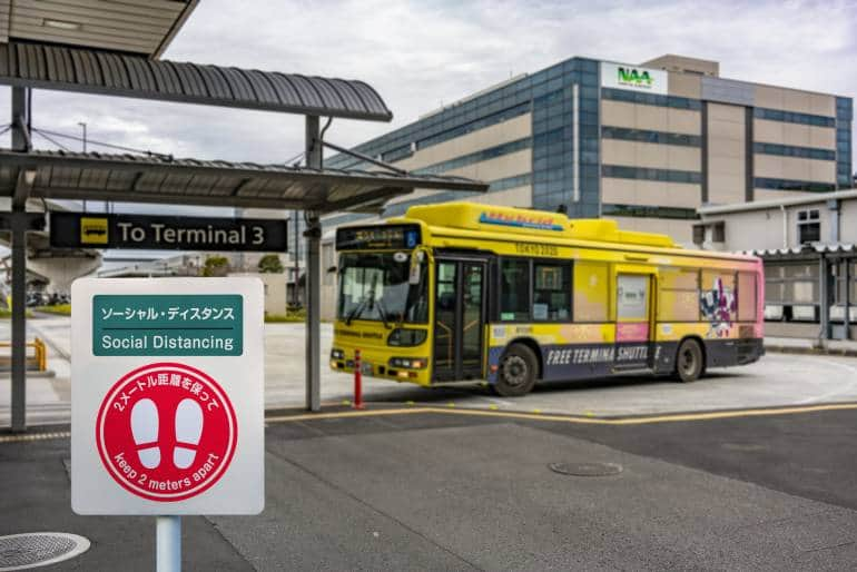 Social distancing sign at the bus stop in terminal 3 of Narita International Airport with a shuttle bus