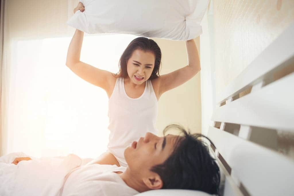 woman holding pillow above snoring partner in bed