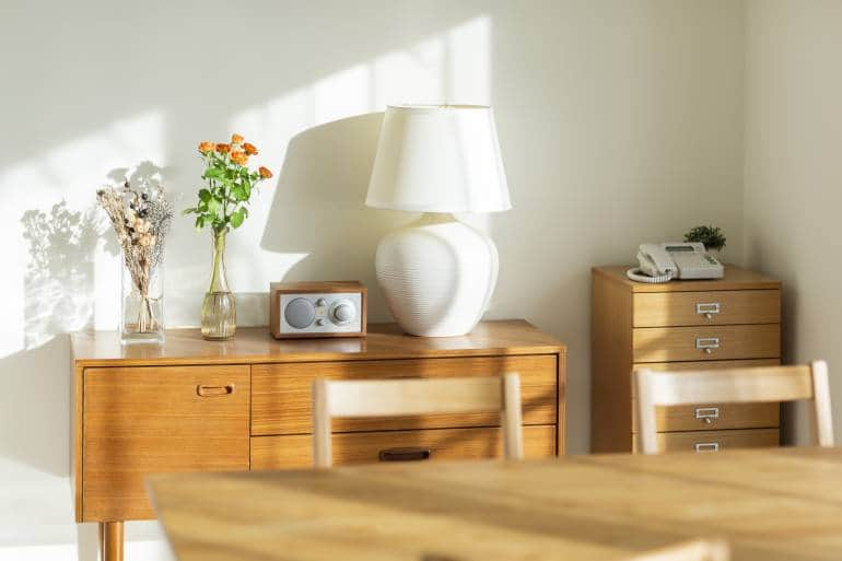 wood storage chest with lamp, speaker and vase of flowers