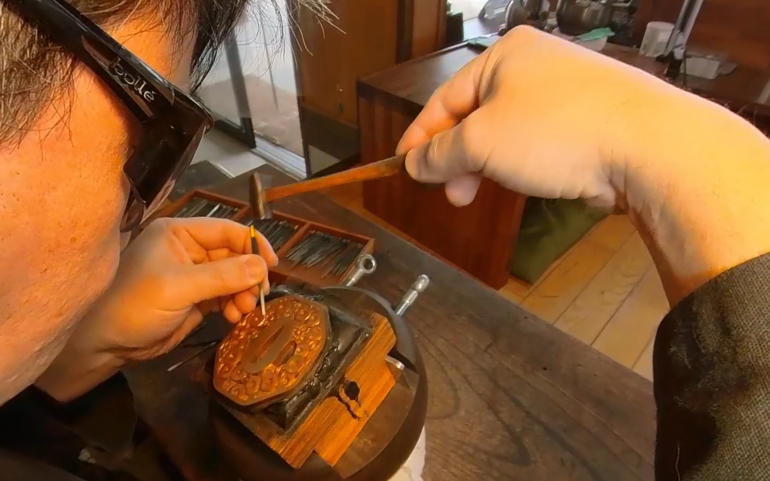 man with work goggles engraving a sword