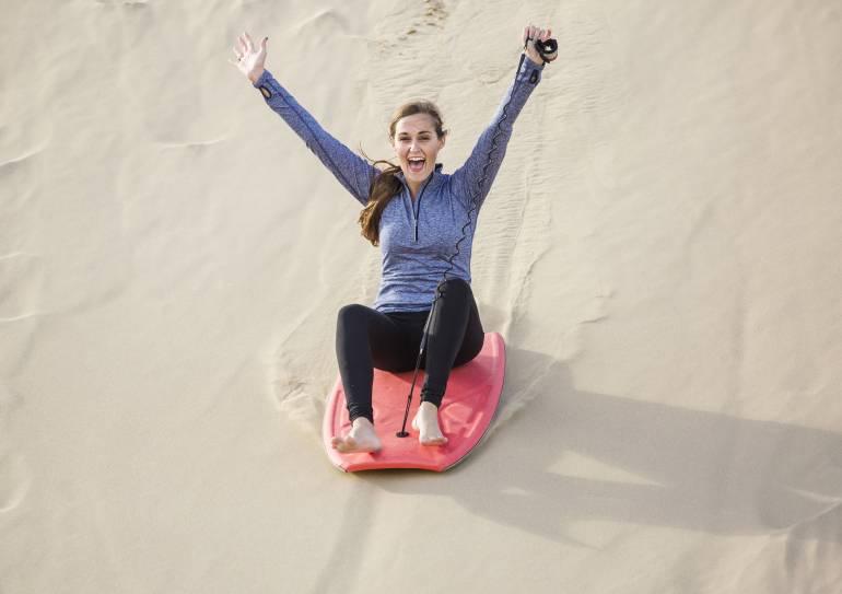 young woman sandboarding