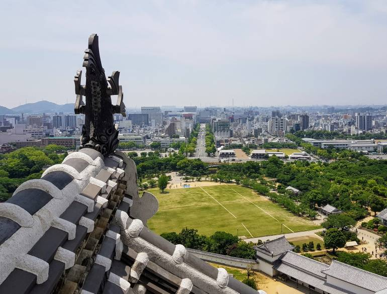 View from the top floor of Himeji Castle along a wide avenue towards Himeji Station. In the foreground is part of the castle roof while in the middle foreground is the green expanse of Himeji Park.