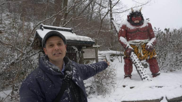 John standing near an oni statue