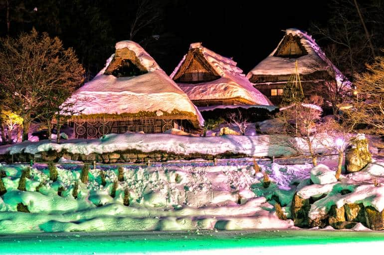 Traditional thatched houses at Hida Folk Village covered in snow and illuminated at night.