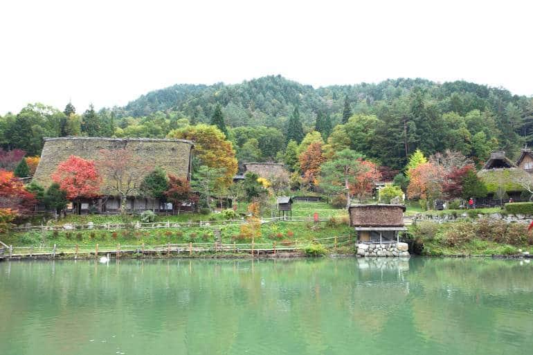 Autumn colored trees and house at lake in Hida Folk Village takayama japan