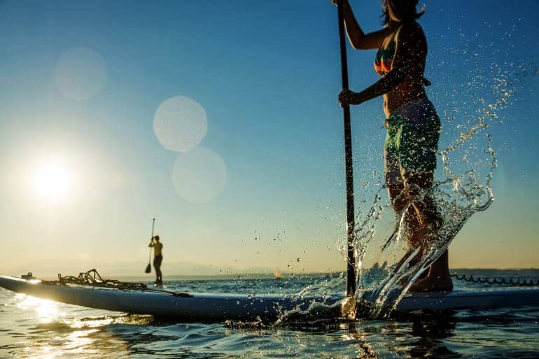 woman on stand up paddle board as the sunsets
