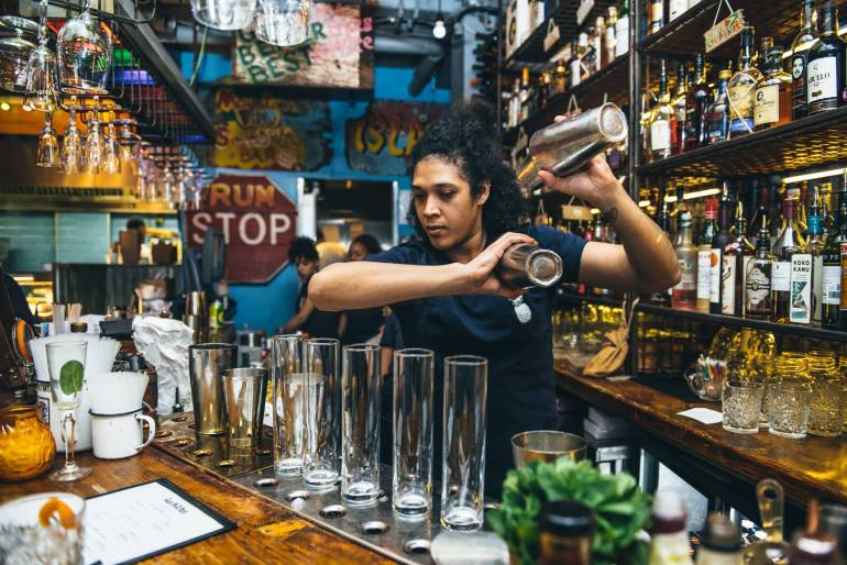 A woman making cocktails in a bar