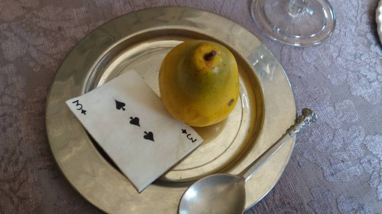An ornamental pear and playing card on a plate