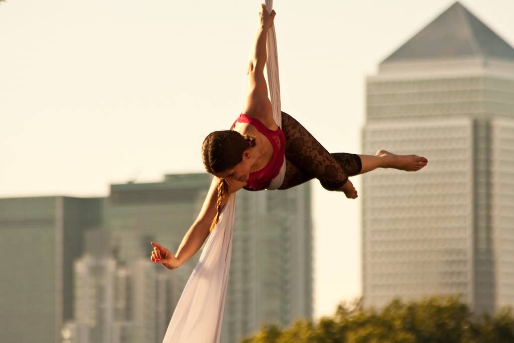Aerial performer in front of London buildings