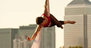 Aerial performer in front of London buildings