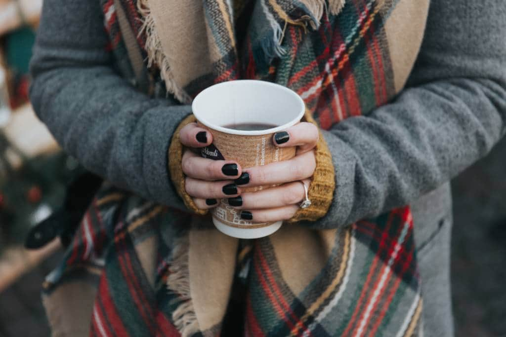 A pair of hands holding a cup of Mulled Wine