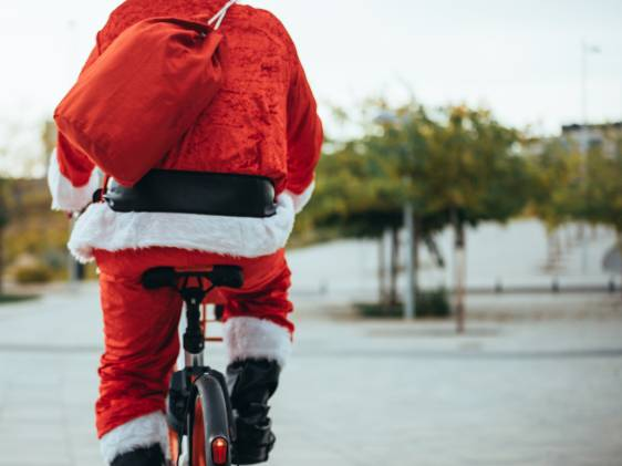 View of Santa Claus' back with bicycle and his red suitcase on his back