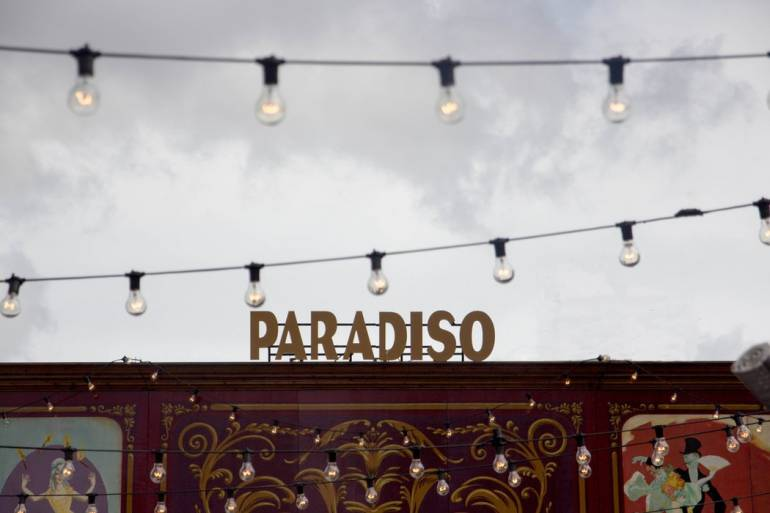 A sign reading Paradiso and some string lights