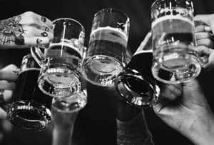 A black and white image of hands toasting with large beer glasses