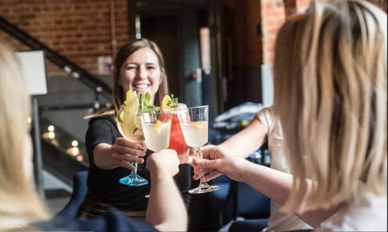 4 women clinking cocktails