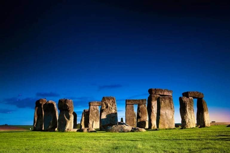 Stonehenge pillars at dusk with a blue-black sky and green grass