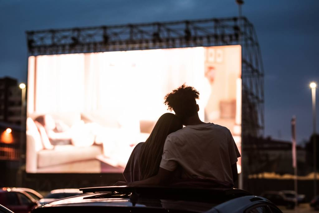 Couple embracing at a drive-in at night
