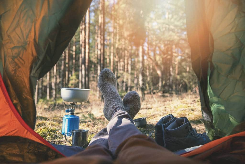 campers feet outside a tent with the view of forest