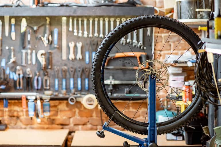 Bicycle workshop with wheel during the aligning process and working tools on the background
