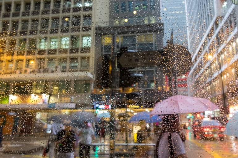 People With Umbrellas Walking By The City Street Under The Rain. Looking Through The Window With Raindrops.